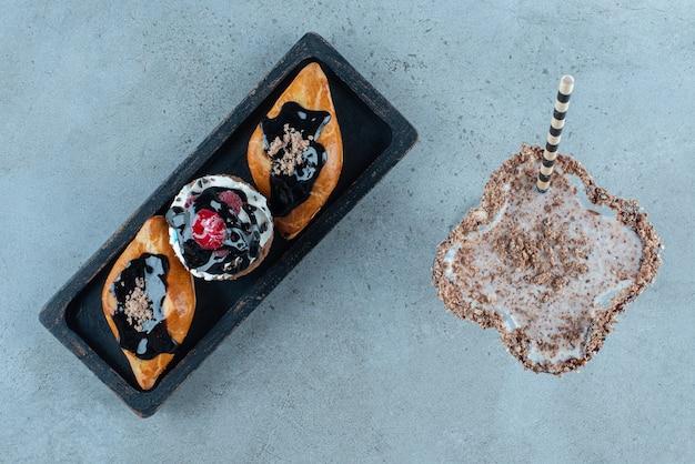 Deliciosa bebida doce com cupcakes em uma placa escura.
