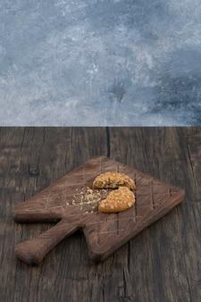 Deliciosa bolacha quebrada com cereais colocada sobre uma tábua de madeira.