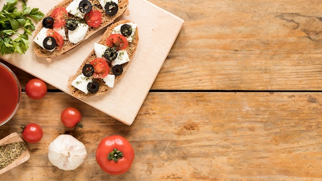 Deliciosa bruschetta na tábua de madeira e ingrediente sobre a mesa de madeira