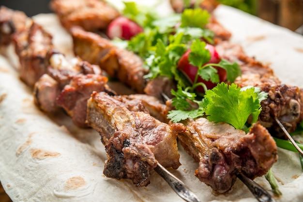 Deliciosa carne grelhada variada com vegetais na mesa de piquenique de prato branco para festa de churrasco em família