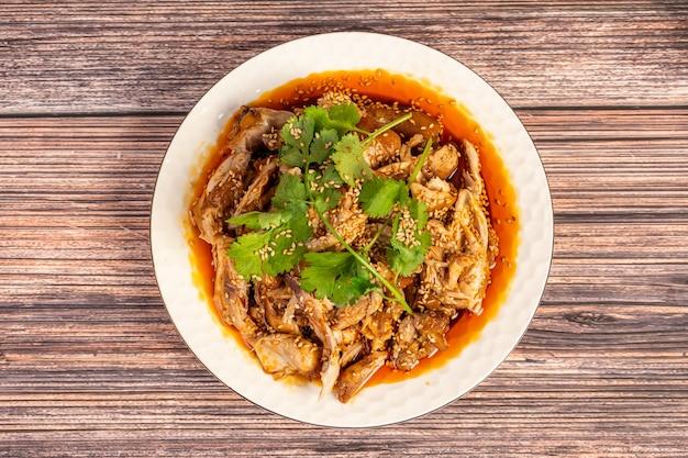 Deliciosa comida chinesa, frango com óleo de pimenta no prato, na mesa de grãos de madeira