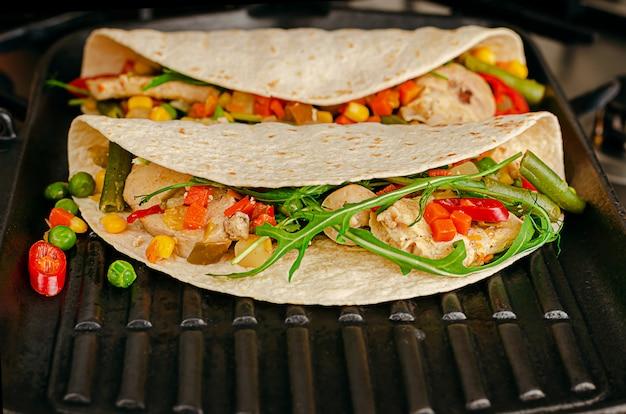 Deliciosa comida mexicana. tacos com legumes e frango na panela de grelhar. copie o espaço