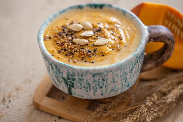 Deliciosa composição com sopa de abóbora em um lindo prato de cerâmica. alimentos sazonais.