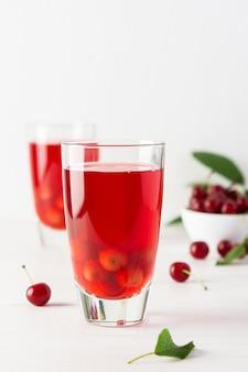 Deliciosa compota de cereja de verão com polpa em copos em um fundo branco