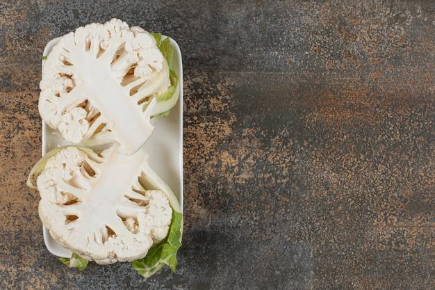 Deliciosa couve-flor fatiada na tigela, na superfície de mármore