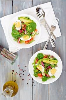 Deliciosa e leve salada de tomate, ovos e uma mistura de folhas de alface. café da manhã saudável. vista do topo