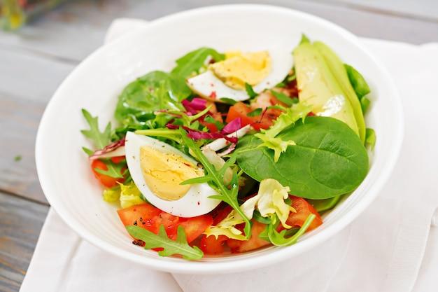 Deliciosa e leve salada de tomate, ovos e uma mistura de folhas de alface. café da manhã saudável.