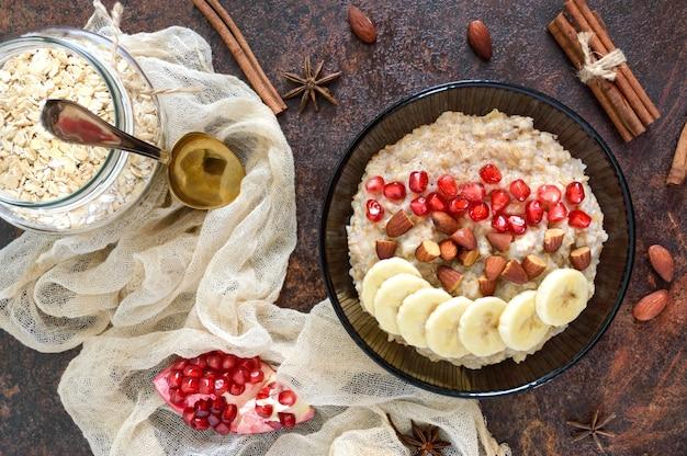 Deliciosa e saudável aveia com banana, sementes de romã, amêndoa e canela. café da manhã saudável. comida de fitness. nutrição apropriada. postura plana. vista do topo.
