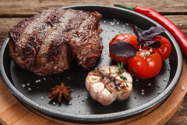 Deliciosa estaca beaf servida com tomates grelhados e alho e decorada com manjericão e pimenta, vista do close up.