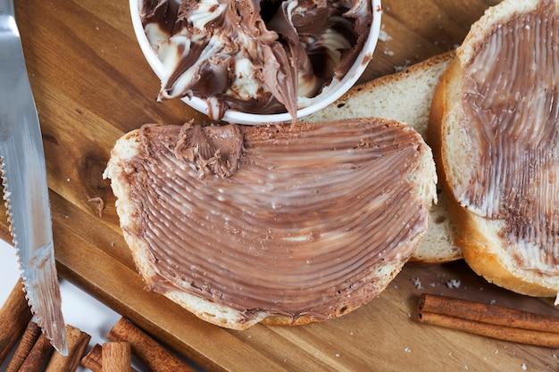 Deliciosa manteiga de chocolate e pão branco, fatias de pão branco com manteiga de chocolate espalhada, pasta de chocolate natural com cacau durante o café da manhã, close up