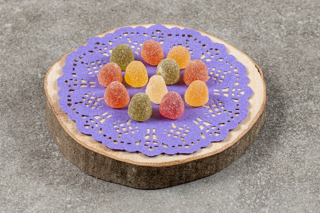 Deliciosa marmelada colorida, na placa de madeira.