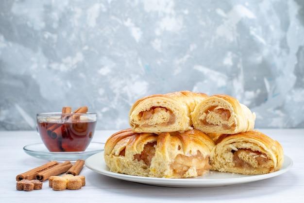 Deliciosa massa assada com recheio doce fatiado e inteiro junto com biscoitos e chá na mesa branca, biscoito biscoito bolo doce chá
