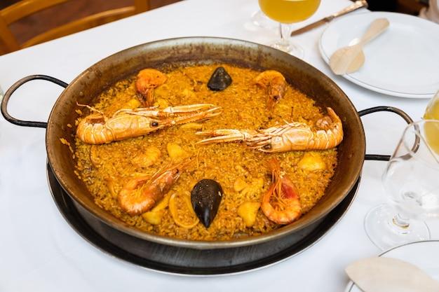 Deliciosa paella tradicional valenciana de frutos do mar. prato saboroso de arroz com camarões, lulas e amêijoas na panela de paella