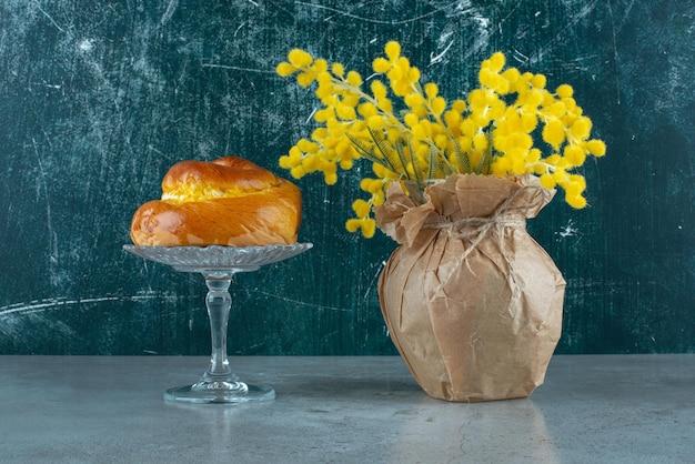 Deliciosa pastelaria doce e flores amarelas em mármore.