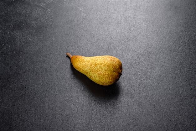 Deliciosa pêra amarela madura suculenta fresca em um fundo escuro de concreto