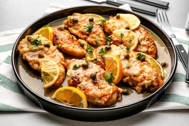 Deliciosa piccata de frango com molho e limão no prato