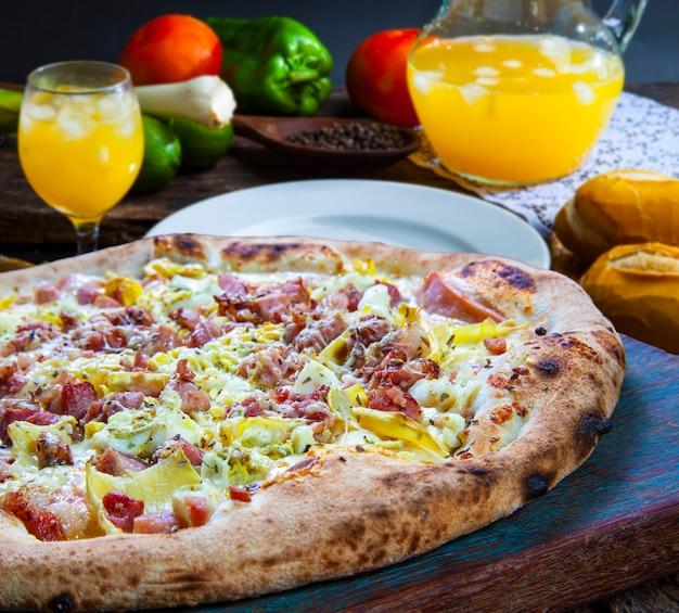 Deliciosa pizza assada com bacon e suco de laranja