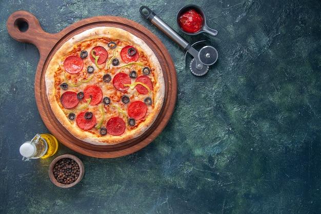 Deliciosa pizza caseira com tomate em tábua de madeira e ketchup de pimenta em garrafa de óleo no lado direito em superfície escura