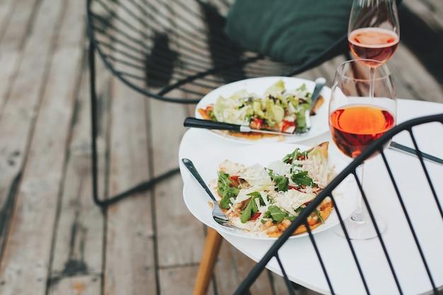 Deliciosa pizza caseira e bebida aperol na mesa moderna no terraço de madeira na casa de campo, jantar para dois. saborosos jantares e coquetéis para festa em casa ao ar livre