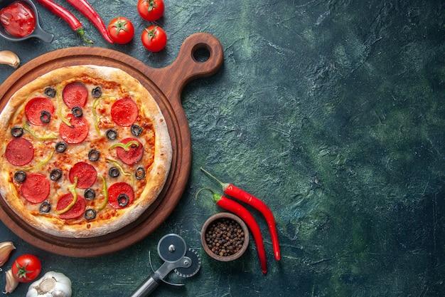Deliciosa pizza caseira em uma tábua de madeira e tomate, alho e pimenta no lado direito, em superfície escura isolada
