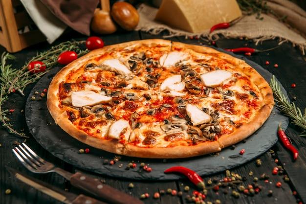 Deliciosa pizza com cogumelos e frango no quadro negro na mesa de madeira escura com ervas e tomates