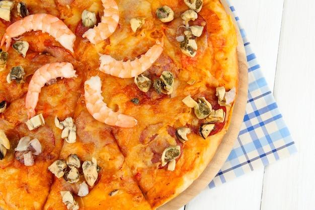 Deliciosa pizza com frutos do mar em suporte de madeira