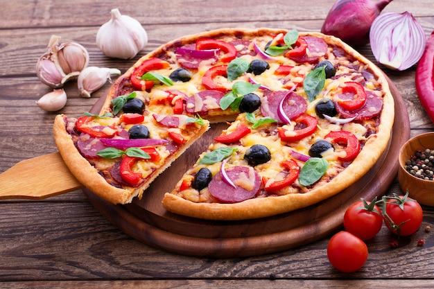 Deliciosa pizza com ingredientes na mesa de madeira