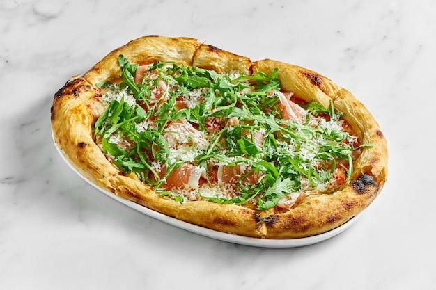 Deliciosa pizza com presunto, molho de tomate, parmesão e rúcula em um prato branco sobre um fundo de mármore branco