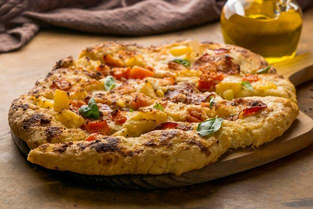 Deliciosa pizza cozida na tábua de madeira com óleo