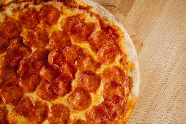 Deliciosa pizza de calabresa servida em prato de madeira