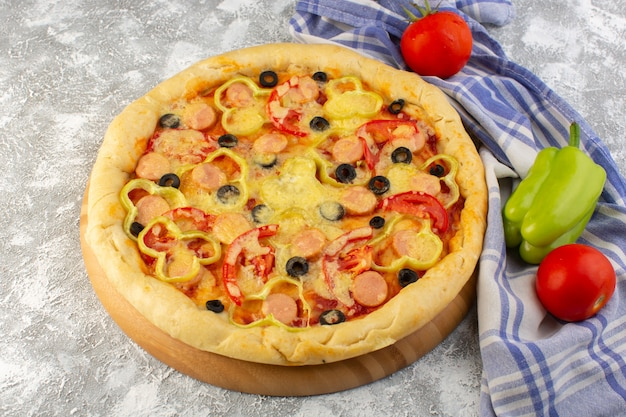 Deliciosa pizza de queijo com azeitonas, salsichas e tomates na mesa leve fast-food comida italiana massa
