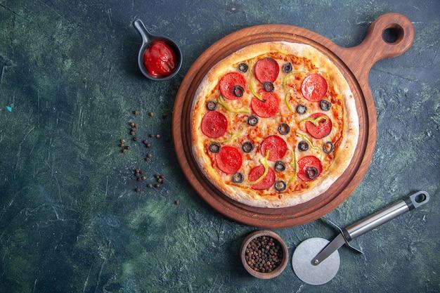 Deliciosa pizza em uma tábua de madeira e ketchup de pimenta do lado esquerdo em uma superfície escura isolada
