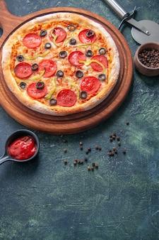 Deliciosa pizza em uma tábua de madeira e ketchup de pimenta em uma superfície escura isolada em visão vertical