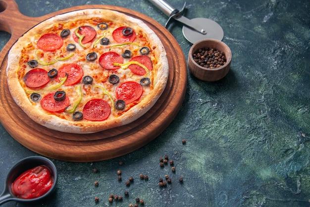 Deliciosa pizza em uma tábua de madeira e ketchup de pimenta em uma superfície escura isolada em vista de perto