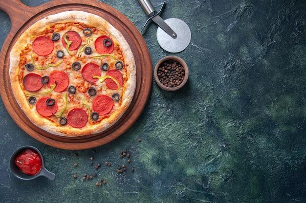 Deliciosa pizza em uma tábua de madeira e ketchup de pimenta em uma superfície escura isolada