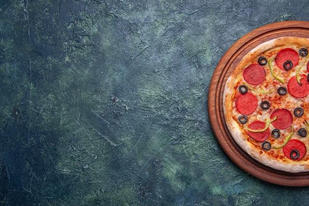 Deliciosa pizza em uma tábua de madeira no lado esquerdo em uma superfície escura isolada com espaço livre na metade do tiro