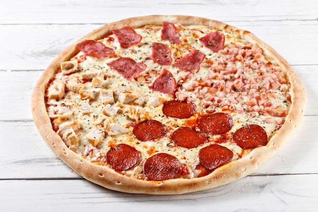 Deliciosa pizza fresca 4 em 1 com diferentes tipos de carne, servida na mesa de madeira