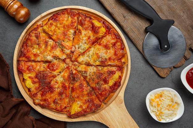 Deliciosa pizza havaiana e ingredientes de cozinha.