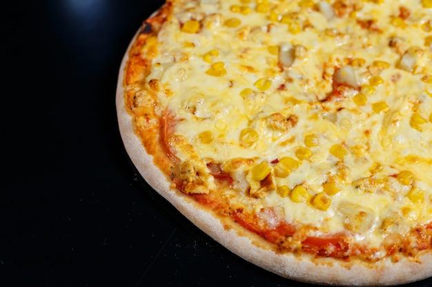 Deliciosa pizza italiana com carne crua, tomate e azeite em uma mesa de concreto escura. vista superior com espaço de cópia.