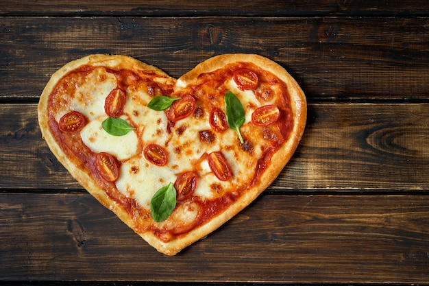Deliciosa pizza italiana em forma de coração na madeira