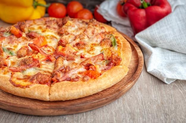 Deliciosa pizza italiana fatiada com bacon, queijo, tomate, capsicum na placa de madeira