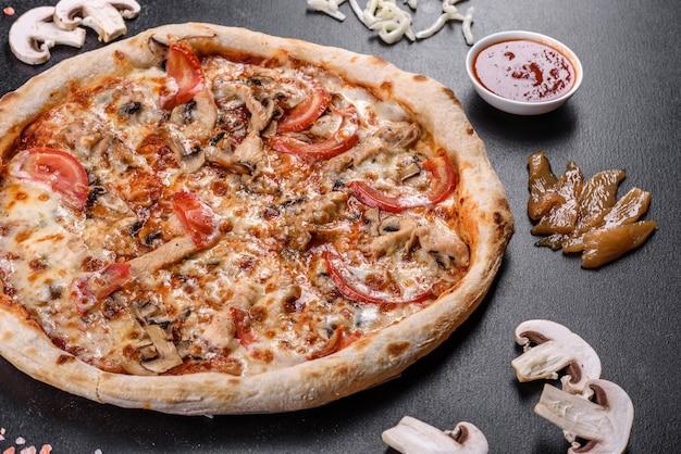 Deliciosa pizza italiana fresca com cogumelos e tomate em um fundo escuro de concreto. cozinha italiana