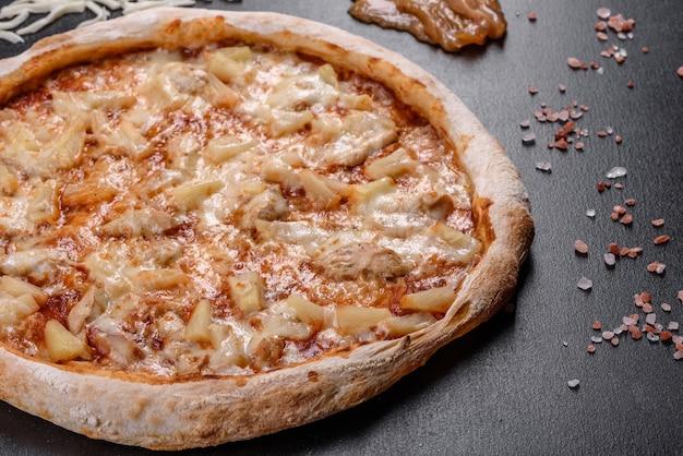 Deliciosa pizza italiana fresca com frango, tomate e abacaxi em um fundo escuro de concreto. cozinha italiana