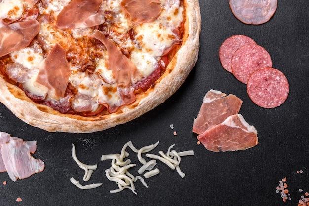 Deliciosa pizza italiana fresca com presunto em um fundo escuro de concreto. cozinha italiana