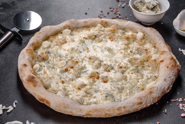 Deliciosa pizza italiana fresca com quatro tipos de queijo em um fundo escuro de concreto. cozinha italiana