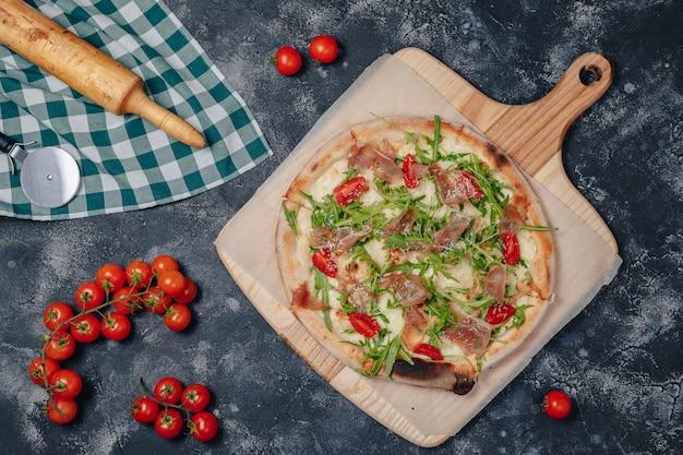 Deliciosa pizza napolitana a bordo com tomate cereja