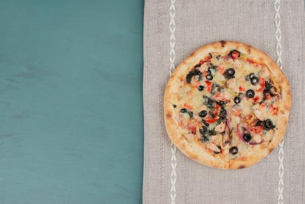 Deliciosa pizza quente com azeitonas e tomates na superfície azul.