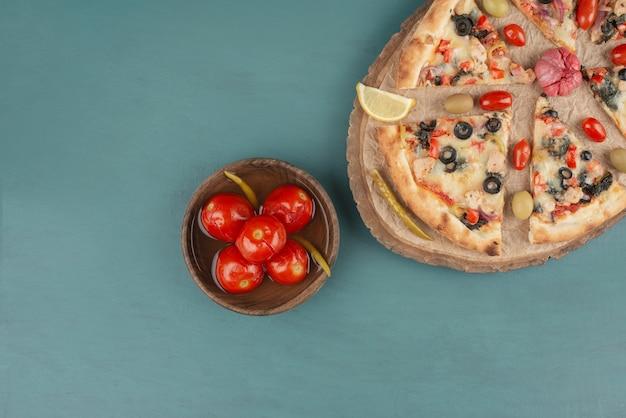 Deliciosa pizza quente e tigela de tomate em conserva na mesa azul.