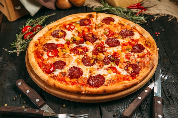 Deliciosa pizza saborosa com calabresa e pimenta no quadro negro sobre o fundo escuro de madeira