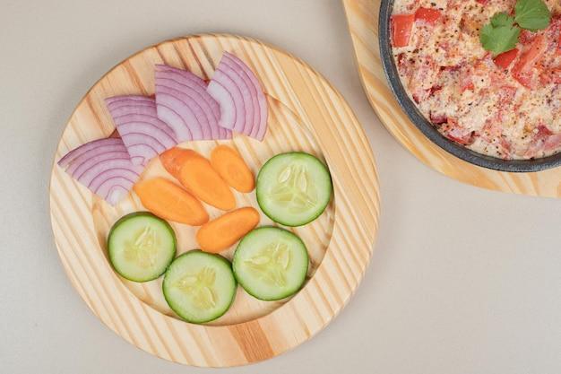 Deliciosa refeição com vegetais fatiados na placa de madeira.